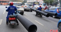 Well, this looks safe: Workers transport huge pipes on motorbikes